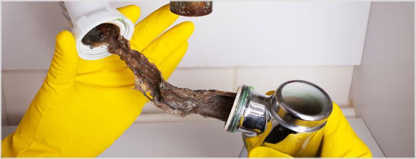 Grobe Verschmutzungen wie Haare sollten Sie aus dem Abfluss ziehen - entweder durch Demontage des Siphons oder mit Hilfe eines Kabelbinders.