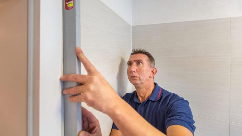 Der Fachmann prüft, ob die Wand gerade ist